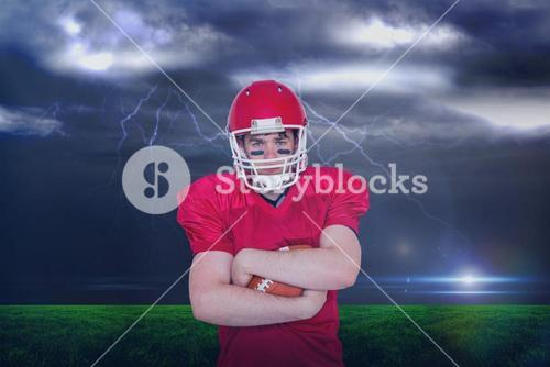 Composite image of american football player with arms crossed