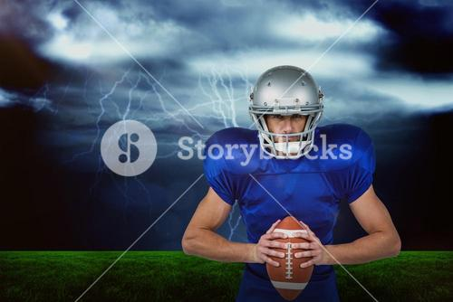 Composite image of confident american football player holding ball
