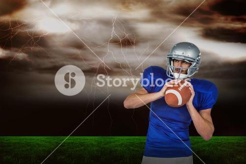 Composite image of american football player holding ball white looking away