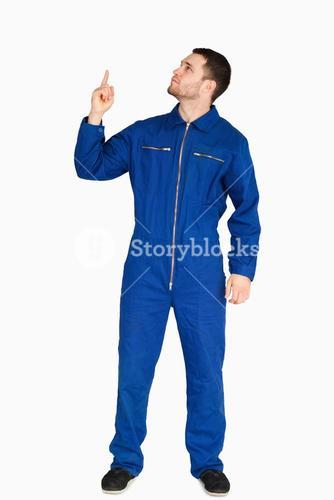 Young mechanic in boiler suit pointing up