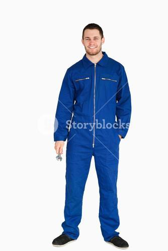 Smiling young mechanic in boiler suit holding a wrench