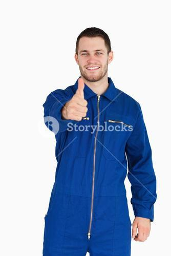 Smiling young mechanic in boiler suit giving thumb up