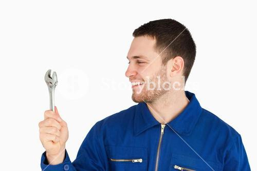 Smiling young mechanic in boiler suit looking at his wrench