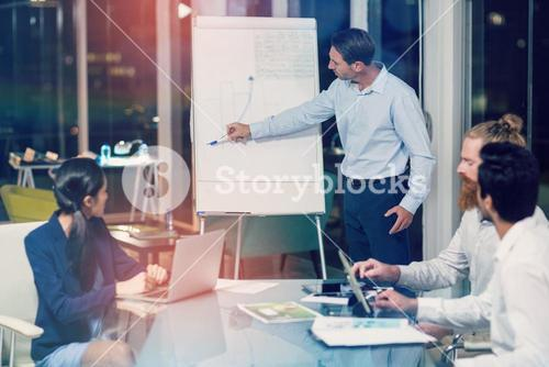 Businessman discussing graph on white board with colleagues