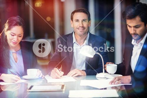 Businessman smiling while colleagues writing on paper