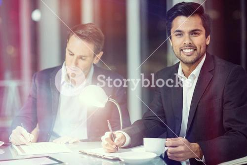 Businessman smiling while colleague writing on paper