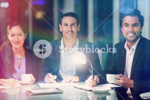 Group of businesspeople smiling while having coffee