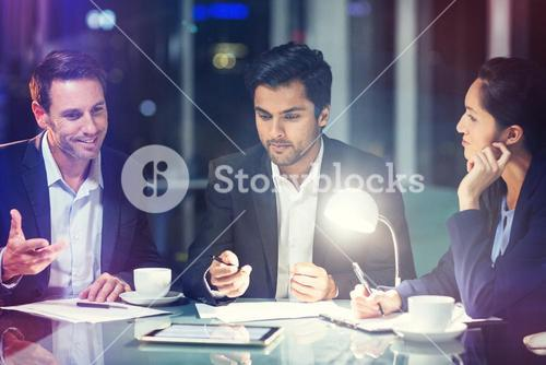Group of businesspeople discussing over digital tablet