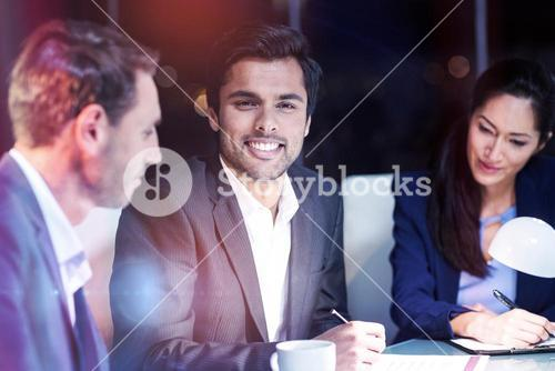 Businessman smiling while colleagues looking at document