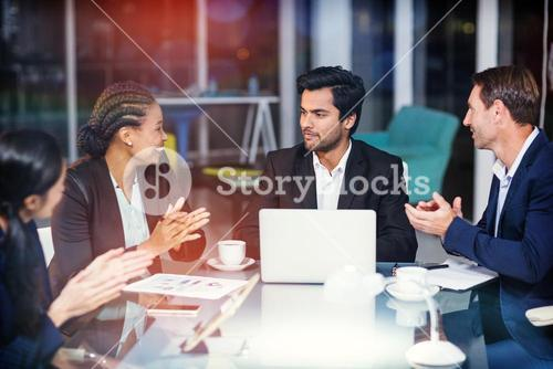 Coworkers applauding colleague at meeting