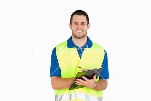 Smiling young delivery man completing delivery note