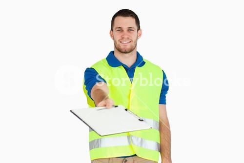 Smiling young delivery man asking for signature on delivery bill