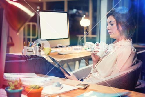 Businesswoman using digital tablet while sitting at desk