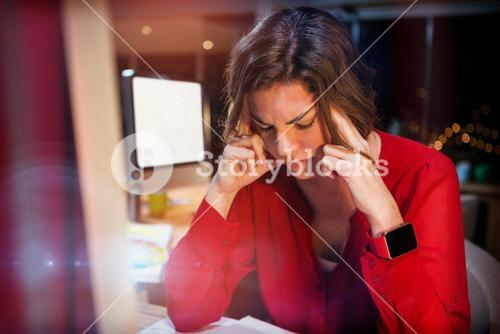 Stressed businesswoman sitting by computer