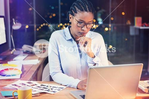 Thoughtful businesswoman working on laptop
