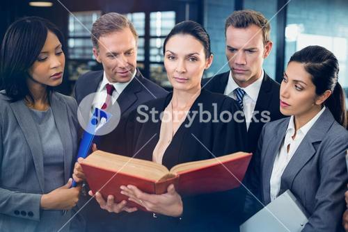 Lawyer reading law book and interacting with business people