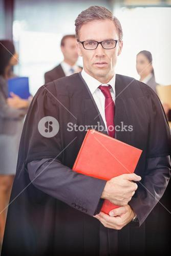 Portrait of lawyer holding law book while standing