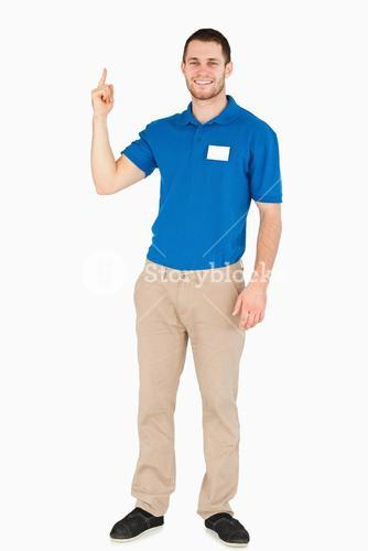 Smiling young salesman pointing upwards
