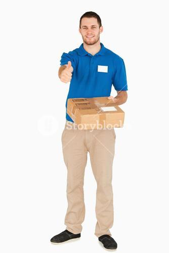 Smiling young salesman with parcel giving thumb up