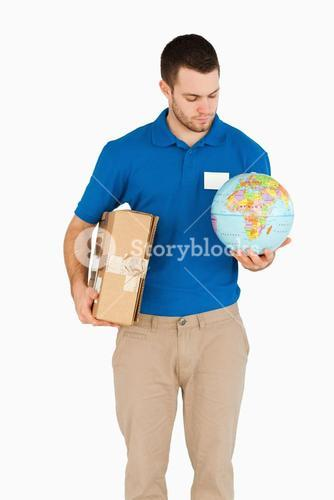 Young salesman with packet and globe in his hands