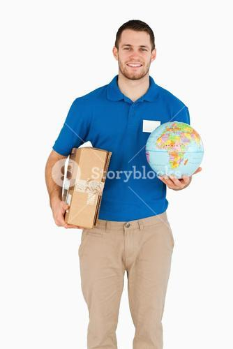 Smiling young salesman with parcel and globe in his hands