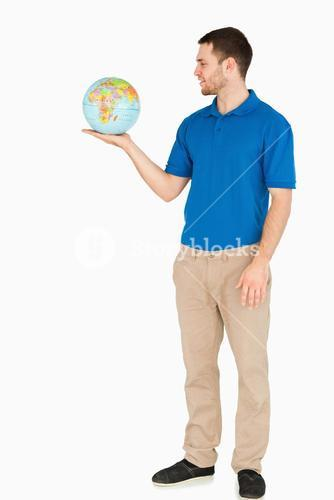 Young salesman holding globe in his palm