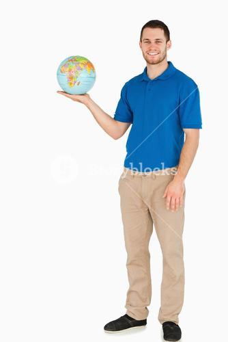 Smiling young salesman holding globe in his palm