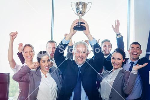 Winning business team with an executive holding trophy