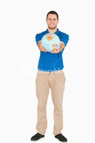 Smiling young salesman presenting globe in his hands
