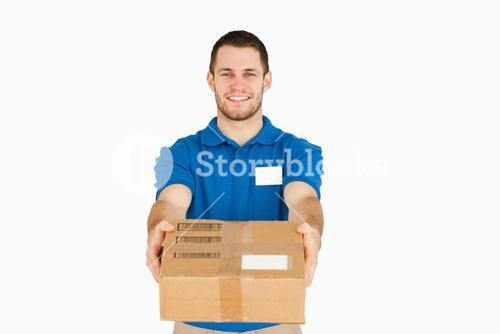 Smiling young salesman handing over packet