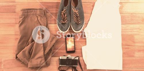 Composite image of beach accessories and clothes on wooden board