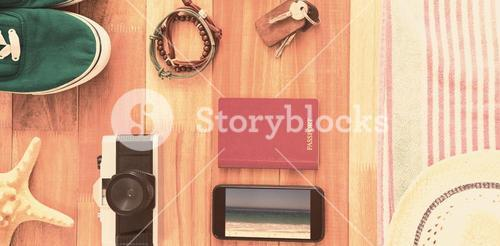 Composite image of accessories and travel items on wooden board