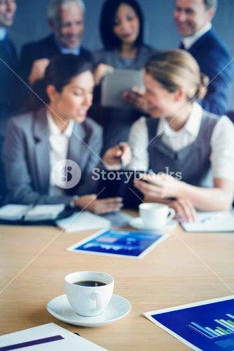 Cup of coffee on table in conference room