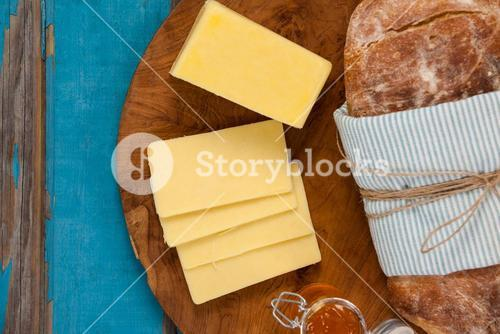 Bread loaf with slices of cheese and sauce on wooden serving board
