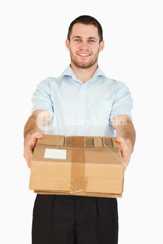 Smiling young post employee handing over parcel