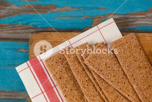 Crispy biscuits with tissue paper on wooden board