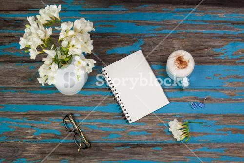 Cup of coffee, flowers in flowerpot, notepad and spectacles placed together