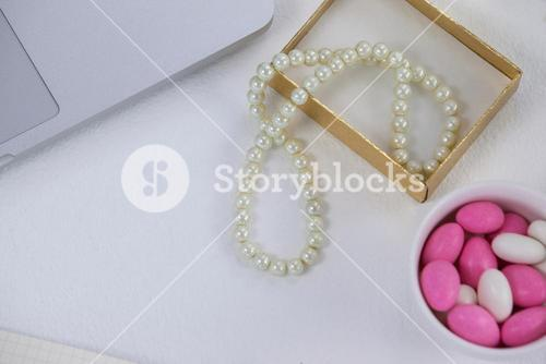Close-up of pearl necklace, pebbles and laptop