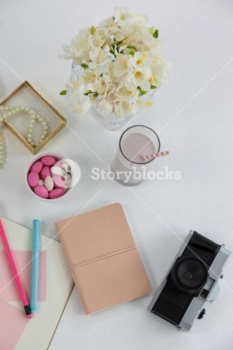 Flowers, diary, camera, glass and pearl necklace