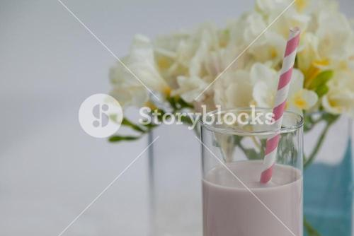 Milk shake in glass with a straw