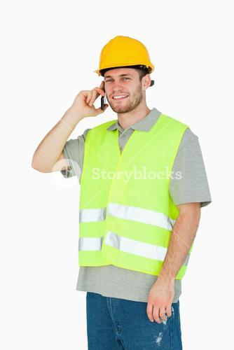 Smiling young construction worker on the mobile phone