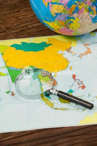 Map, magnifying glass and globe