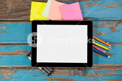 Digital tablet on pens, staple pins, color pencils and sticky notes