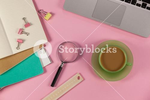 Cup of tea, laptop, magnifying glass, diaries, ruler and paper clips
