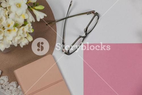 Spectacles, diary, blank page and flowers