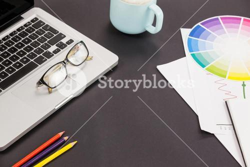 Laptop, spectacles, color pencils, coffee cup and color scheme chart