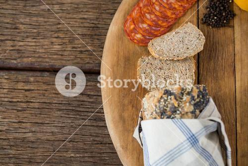 Slices of bread, meat and black pepper on wooden board