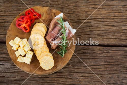 Cheese, red pepper slices, meat and nacho chips on wooden table