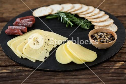 Slices of cheese, nacho chips and rosemary herbs on plate