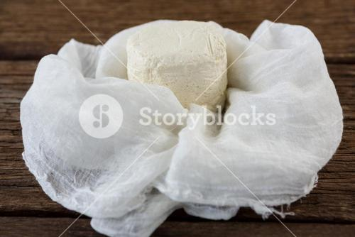 Cottage cheese in white cloth on wooden board